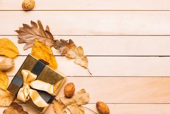 Confezione regalo vicino a foglie e chicchi