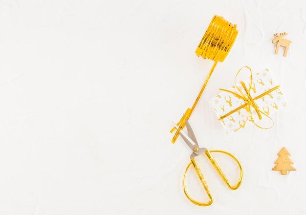 Confezione regalo vicino a forbici, bobina di nastro, cervo decorativo e abete