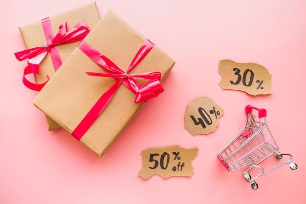 Confezioni regalo con fiocchi rossi vicino carrello della spesa