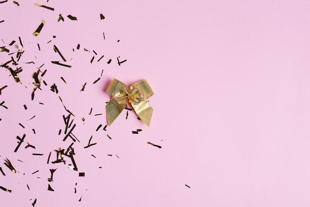Confine d'angolo di saluto da arco dorato e coriandoli luminosi decorativi di carnevale su uno sfondo rosa.