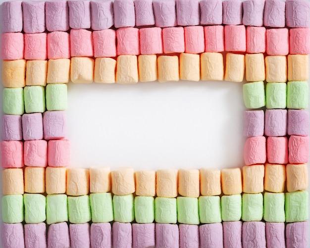 Confine da marshmallow colorato luminoso su sfondo bianco. copia spazio all'interno della cornice. cornice di sfondo mini marshmallow.