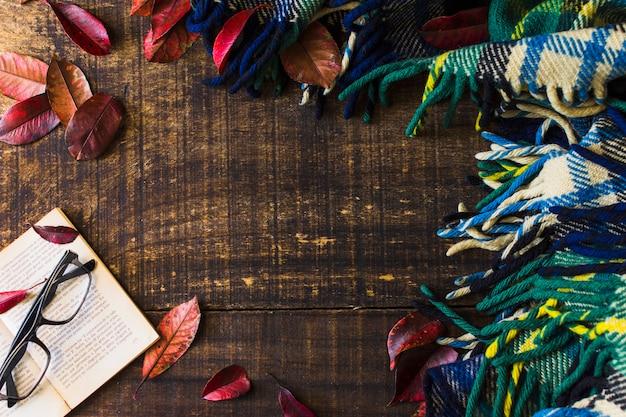 Confine dalla coperta e foglie vicino al libro e occhiali
