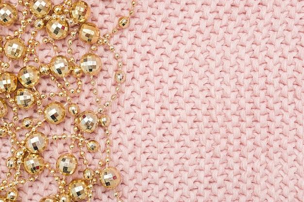 Confine dalla ghirlanda di perle dorate su sfondo rosa a maglia.