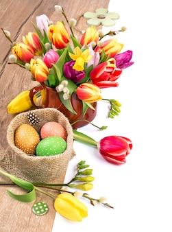 Confine di pasqua colorato con mazzo di tulipani e uova dipinte su legno,