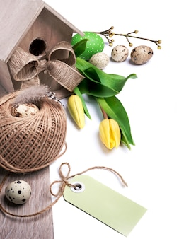 Confine di pasqua con tulipani gialli e decorazioni naturali