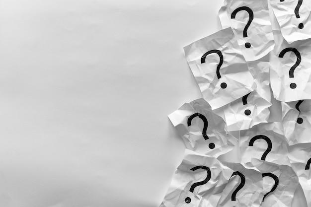 Confine di punti interrogativi spiegazzati su carte