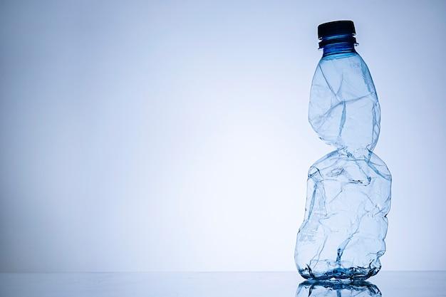 Confine di una bottiglia di plastica trasparente vuota spiegazzata
