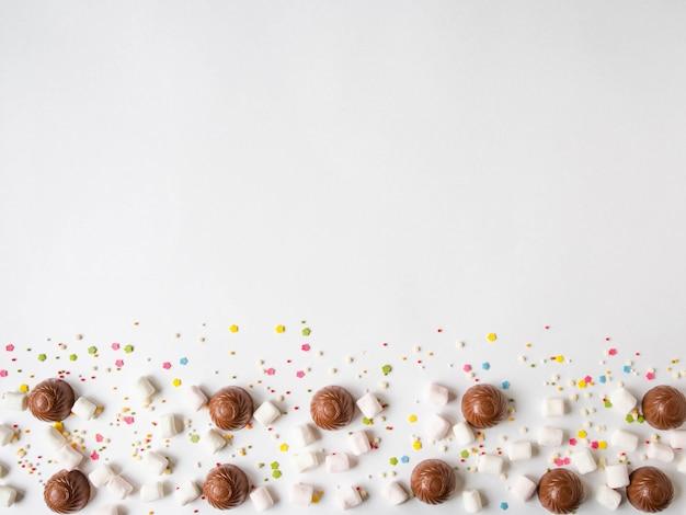Confine festivo dolce della pasticceria con cioccolato, caramelle gommosa e molle e guarnizione della pasticceria sul fondo bianco