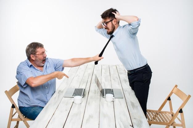 Conflitto commerciale. due uomini che esprimono negatività mentre un uomo afferra la cravatta del suo avversario