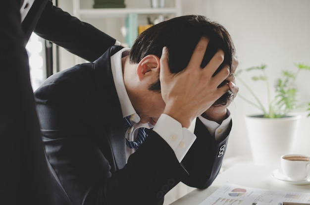 Confortante. uomo d'affari asiatico arrabbiato per problemi con il supporto del suo amico e seduto in ufficio a casa