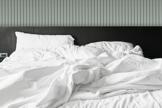 Confortevole camera da letto lenzuola bianche disordinate e piumone disordinato in camera da letto