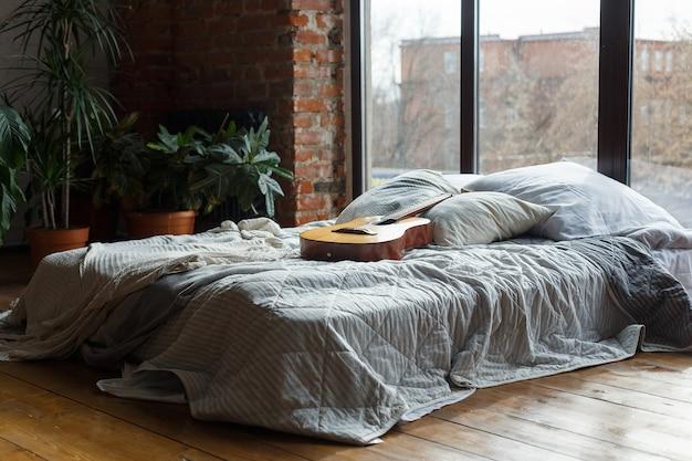 Confortevole interno della camera da letto con ampio letto vicino alle finestre
