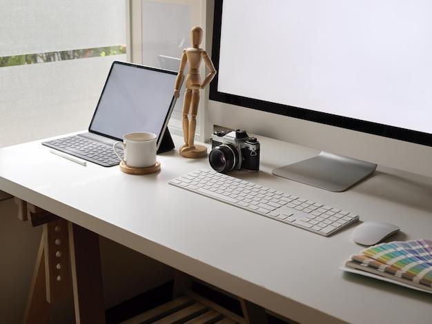 Confortevole scrivania con computer a schermo vuoto, tavoletta digitale, fotocamera, forniture di design e decorazioni accanto alla finestra