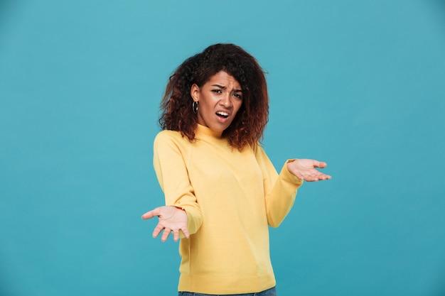 Confusa dispiaciuta donna africana in maglione alza le spalle