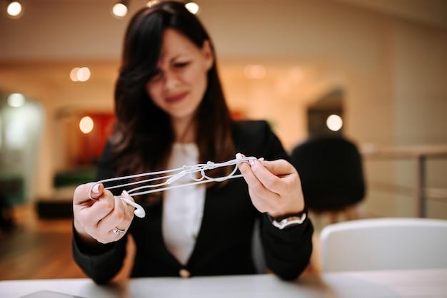 Confusione. chiuda sull'immagine della donna che prova a districare i haphone.