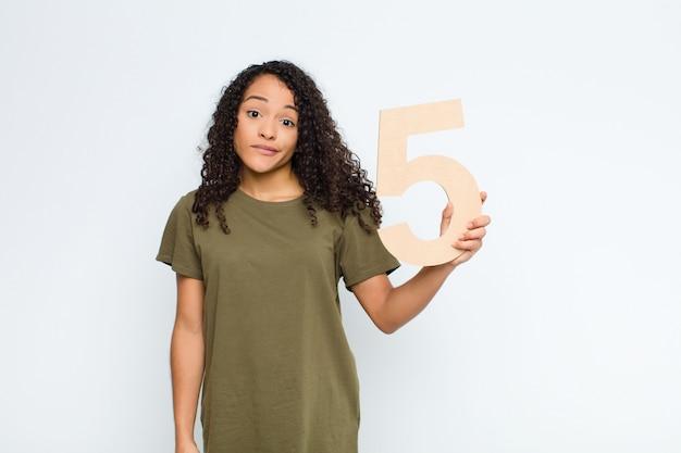 Confuso, dubbioso, pensando, tenendo un numero 5.