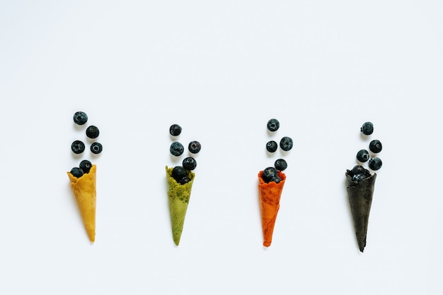 Coni di cialda di gelato di diversi colori farciti con mirtilli isolato su sfondo bianco