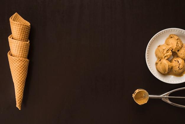 Coni di cialda vicino a palle di gelato sul piatto e scoop