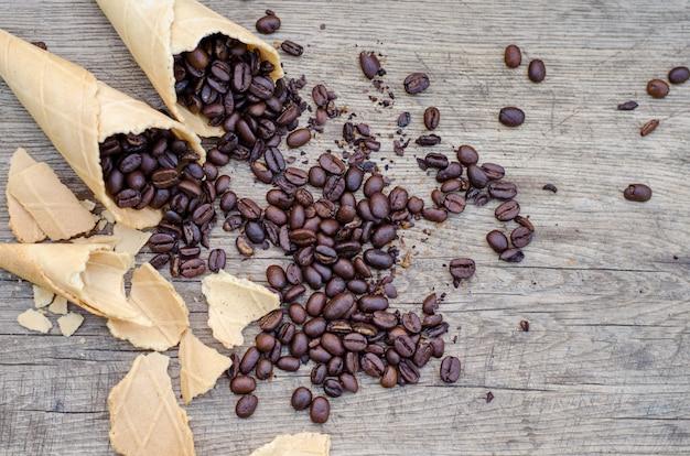 Coni di zucchero con chicchi di caffè sparsi su una parete rustica in legno
