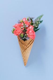 Coni gelato piatti laici con bouquet colorato su blu, copia spazio