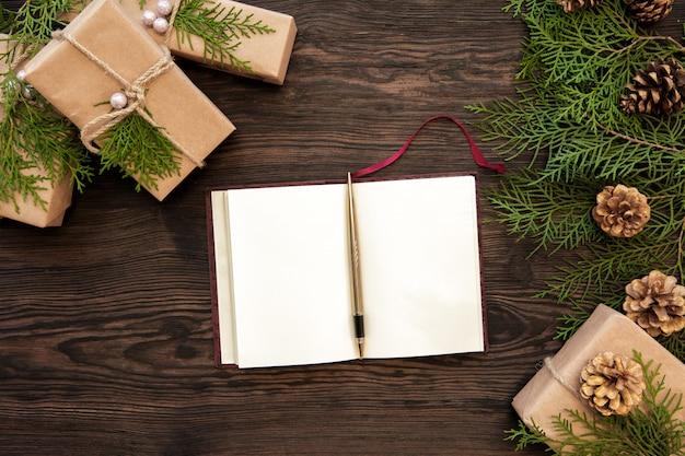 Coni in bianco del taccuino, dei contenitori di regali, del ramo e di abete su di legno. vista dall'alto