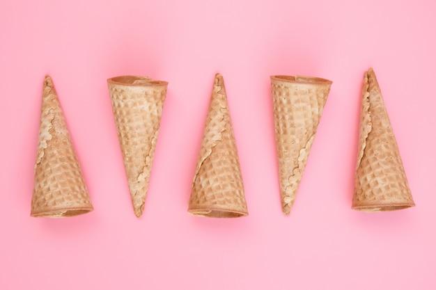 Coni vuoti della cialda del gelato sul rosa.