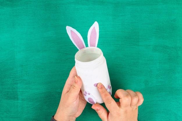 Coniglietto del vaso di pasqua di diy dal barattolo di vetro, feltro, occhi googly su una priorità bassa verde