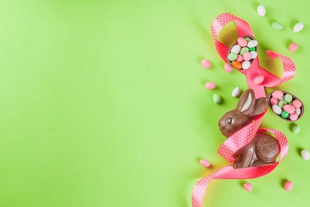 Coniglietto di pasqua al cioccolato, uova di caramella, uova di quaglia e nastro festivo