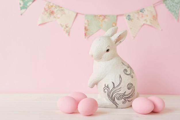 Coniglietto di pasqua con uova e ghirlanda dipinte di rosa