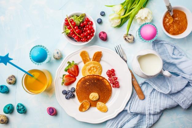 Coniglietto di pasqua di pancake con frutti di bosco. tavolo della colazione di pasqua sfondo blu, vista dall'alto.