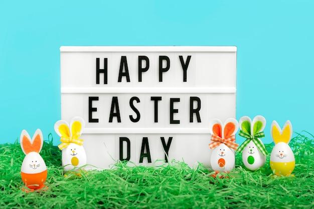 Coniglietto sveglio delle uova di pasqua su backgroung blu. decorazione divertente concetto di buona pasqua