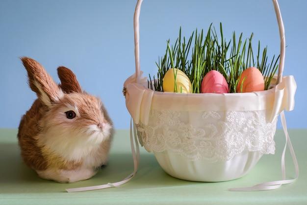Coniglio e uova di pasqua nel cestino
