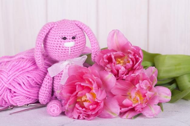 Coniglio rosa con tulipani. decorazioni di san valentino. giocattolo a maglia, amigurumi, biglietto di auguri.