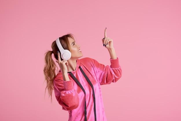 Connessione senza fili. ritratto di posa della giovane donna isolato sopra musica d'ascolto rosa di divertimento con le cuffie.