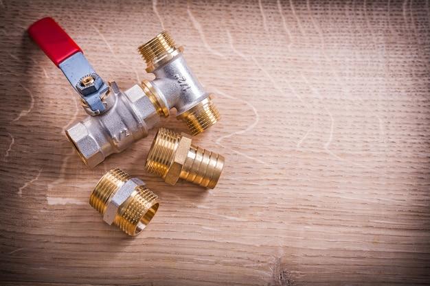 Connettori di tubo d'ottone di vista aerea sul bordo di legno