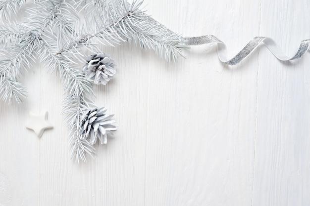 Cono dell'albero di natale del modello e nastro d'argento, flatlay su un bianco