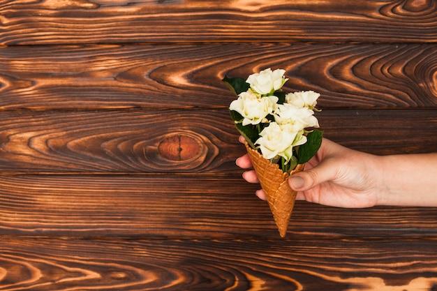 Cono della cialda della holding della persona con le rose bianche