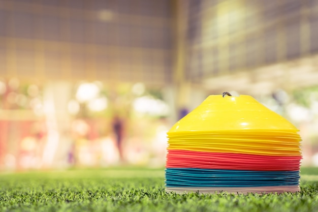 Cono di allenamento sportivo in plastica su campo da calcio indoor