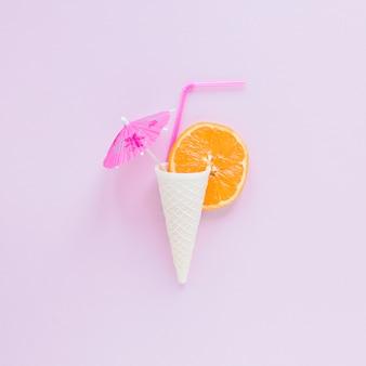 Cono di cialda con arancia, paglia e ombrello sul tavolo