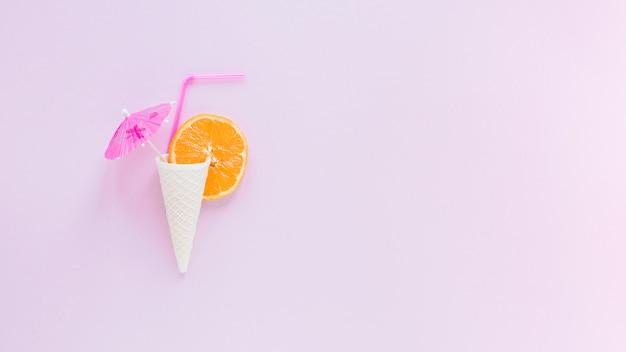 Cono di cialda con arancia, paglia e ombrello