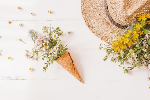 Cono di cialda con fiori selvatici, con cappello di paglia su bianco