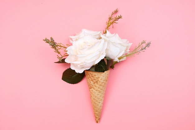 Cono di cialda con fiori sul rosa.
