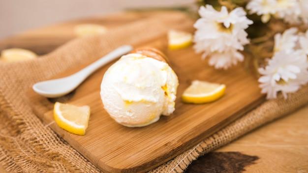 Cono di cialda con gelato vicino a fette di frutta fresca e fiori a bordo