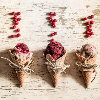 Cono di cialda gelato con frutti di bosco su fondo di legno