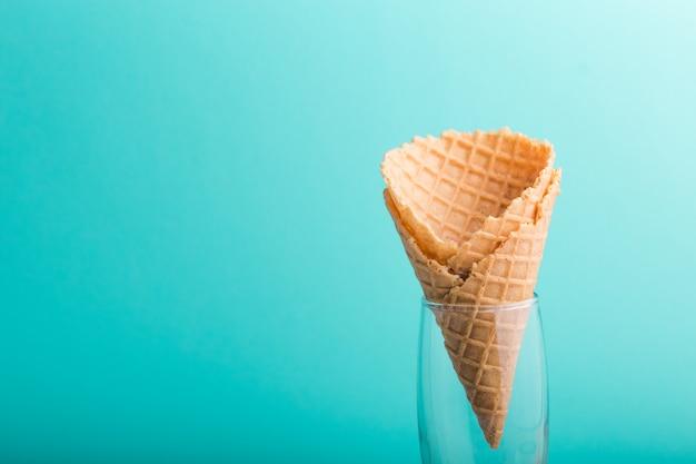 Cono di cialda su sfondo blu. sapore della fragola o del lampone dessert dolce decorato con variopinto spruzza, primo piano