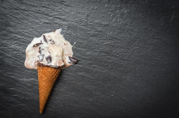 Cono di gelato alla vaniglia con palline di fusione del gelato che scorre gocciolante di cioccolato