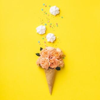 Cono gelato con rose rosa e merengues su giallo