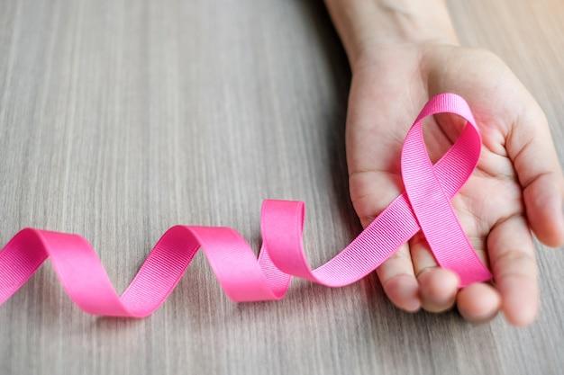 Consapevolezza del cancro al seno, mano della donna che tiene nastro rosa