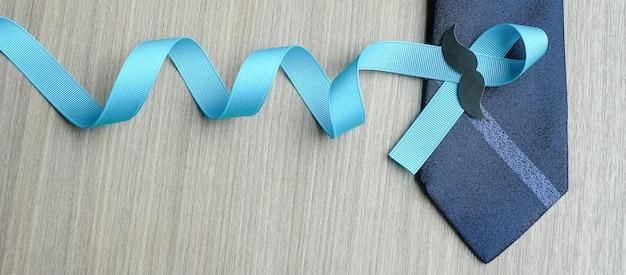 Consapevolezza del cancro alla prostata, nastro azzurro con baffi e cravatta