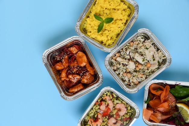 Consegna del cibo. diversi contenitori in alluminio con alimenti naturali dietetici sani. vista dall'alto